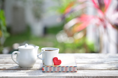 White kettle and cup with notebooks and red heart