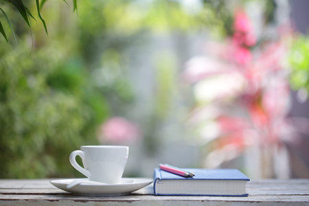White coffee cup with plant and notebooks