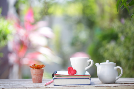 White kettle and cup with red heart and notebooks