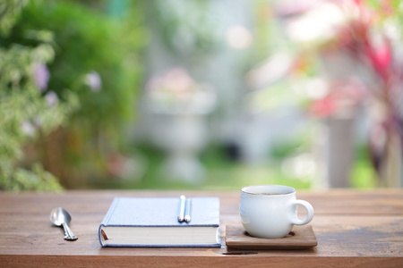 White coffee cup and notebooks on wooden brown table 版權商用圖片