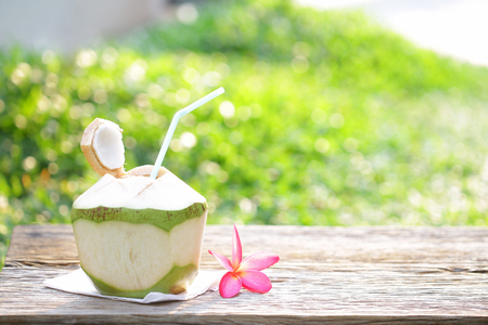 Kokossaft mit rosa Frangipani auf Holztisch im Freien Standard-Bild