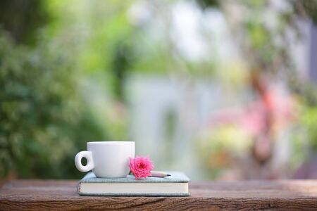 White coffee cup and notebook with pink pygmy rose on wooden table
