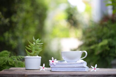 white coffee cup with plant small pot and notebooks with flowers