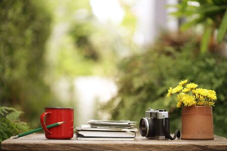 Red coffee cup with diary notebooks and vintage film camera and flower pot on wooden table
