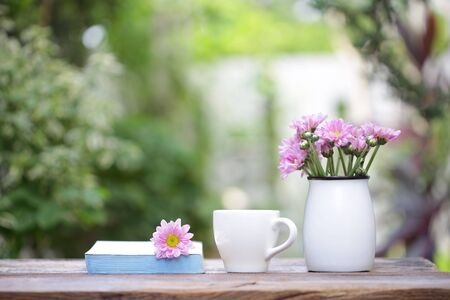 white coffee cup with flower pot on wooden table