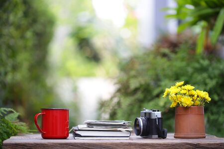 Red coffee cup with diary notebooks and vintage film camera on wooden table