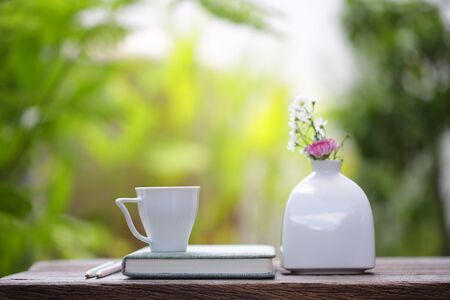 White coffee cup with flower in white vase pot and notebook on wooden table 스톡 콘텐츠