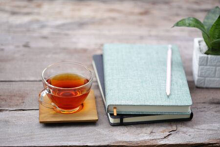 Red tea in transparent glass with notebooks and pencil and plant pot on rustic wooden table