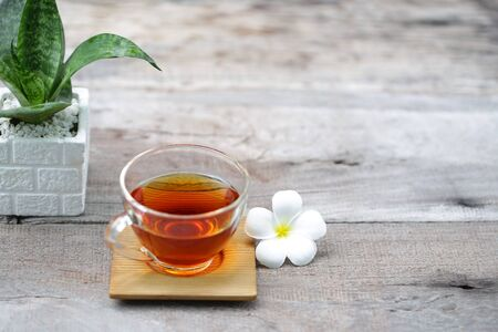 Red tea in transparent glass with flower and plant pot on rustic wooden table Stok Fotoğraf