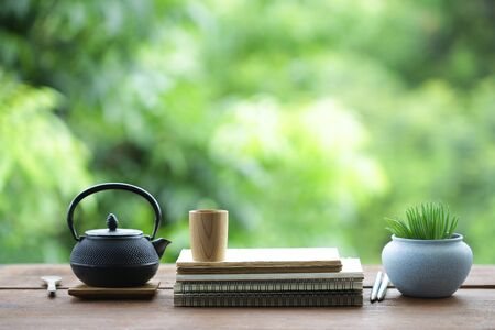 Black teapot with wooden cup with plant pot and notebooks on wooden table Stockfoto