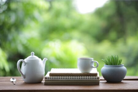 tea cup and tea pot with small plant pot and diary notebook on wooden table Stockfoto - 131290947
