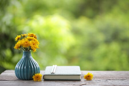 Yellow chrysanthemum flower in blue pot with notebooks and pencil on wooden table Stockfoto