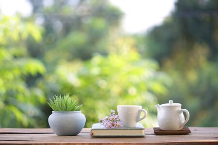 White cup with teapot and small plant with purple daisy flower and book on wooden table