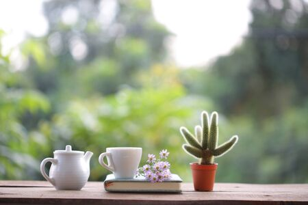 White cup with teapot and book on wooden table 스톡 콘텐츠