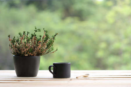 Black coffee mug with heathers plant in black pot on wooden table at outdoor