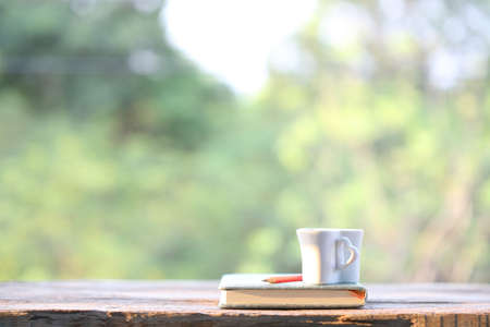White cup with notebook on wooden table with nature view