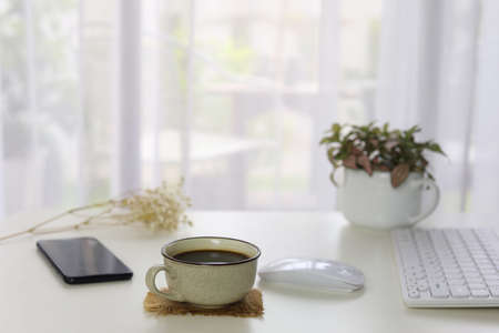 Interior house modern decor with smartphone coffee and white keaboard and mouse and plants pot with see through curtain