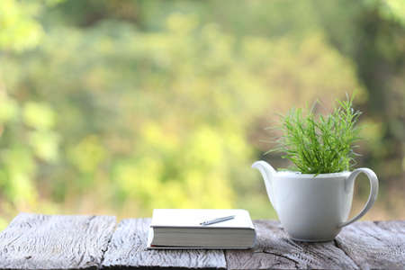 White ceramic plant pot and notebook with pencil on rustic wooden table