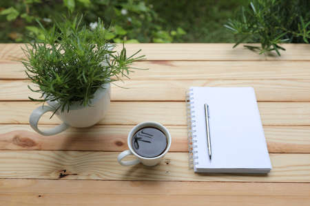 Coffee with white notebook and green plant on wooden table at exterior