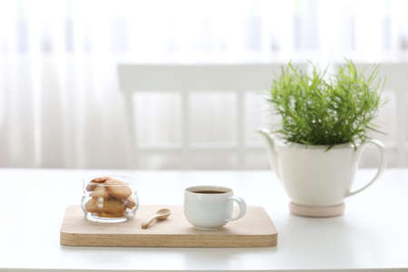 Coffee with cookies on white desk with green plant pot minimal cozy home Banque d'images - 157130478