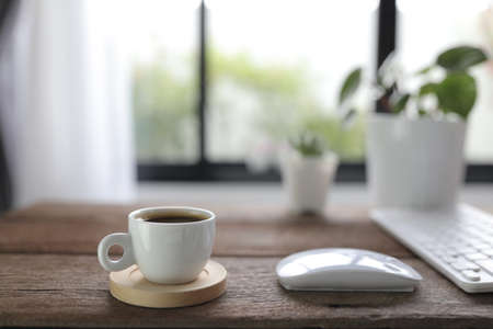 White coffee cup with mouse and keyboard on rustic wooden dinning table interior home