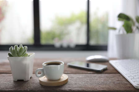 White coffee cup with mouse and keyboard and phone with small succulent plant on rustic wooden dinning table interior home