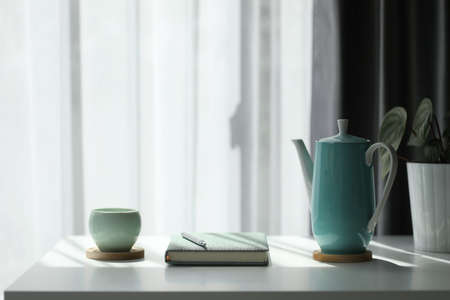 Teal cup and tall teapot with notebook and silver pen on white table cozy workplace