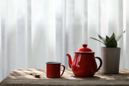 Red coffee cup and teapot with snake plant on brown rustic wooden table with soft see thought curtain