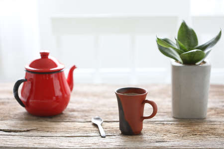 Red coffee cup and teapot with snake plant on brown rustic wooden table