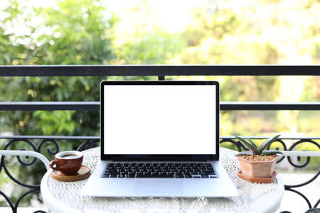 Laptop with coffee cup and plant pot on metal table at corridor