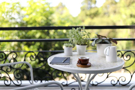 Small coffee cup with white plant pots with notebook on white table at balcony