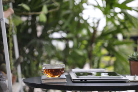 Tea cup glass and tablet on black wooden table at outdoor