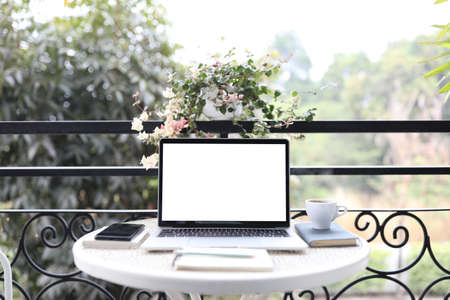 Laptop white mock up blank screen and notebooks on white table outdoor