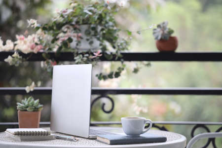 Coffee cup and laptop and notebook on white metal table at balcony Banque d'images