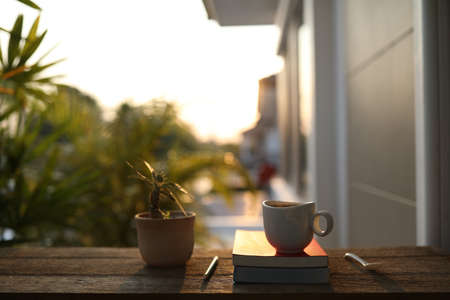 Coffee cup and notebook and pencil with plant pot on brown wooden table at outdoor Banque d'images