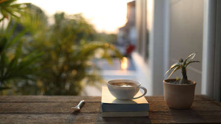 White coffee cup with spoon and notebooks and plant pot on brown wooden table under sunset Banque d'images