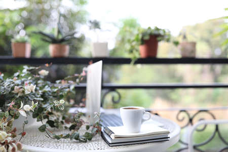 Laptop side view white mock and coffee cup with notebooks on white table outdoor
