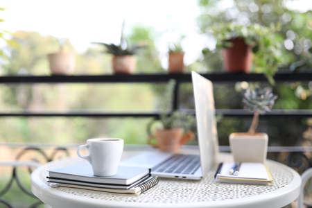 Silver laptop side view white mock and coffee cup with notebooks on white table outdoor Banque d'images