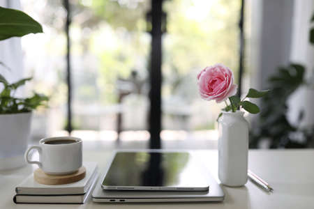 Coffee cup and vase of rose with tablet on wooden table indoor