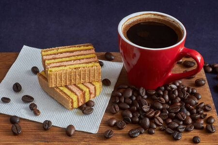 cup of coffee on the board with dessert and coffee beans in natural light