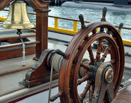 helm: A Sailing Ships Bell and Wheel  Stock Photo