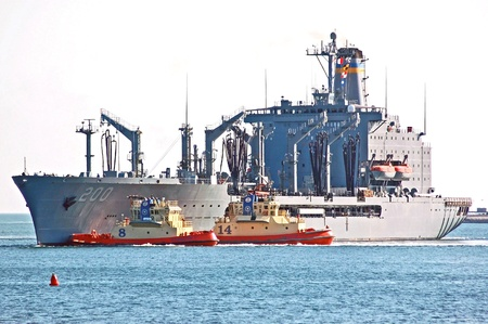 San Diego, California, October 26, 2011: Harbor tugs maneuver the USNS Guadalupe into position in San Diego Bay.