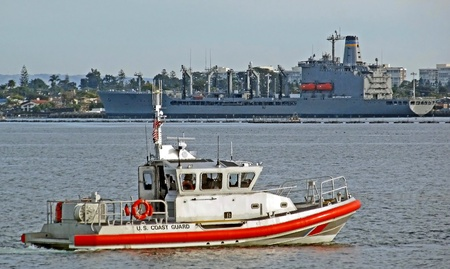 A U.S. Coast Guard RHIB patrols with a naval supply ship in the background. photo