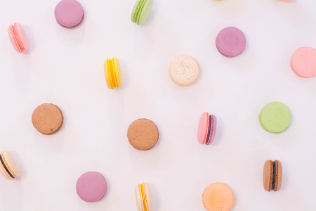 Real macaron cookies scattered over white background. Reklamní fotografie