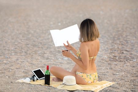 woman reading book at the beach Stock Photo