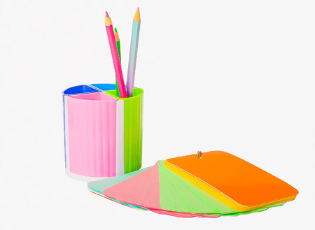 fine tip: Notebook of colored paper and plastic cup with crayons on white background