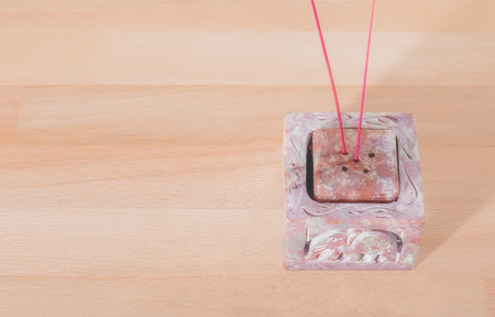 candleholder: Carved stone pink candle-holder on the wooden table