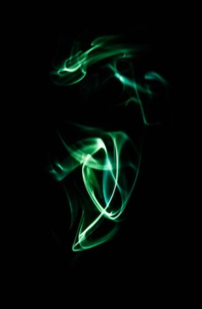 coloured background: Green smoke from the incense on a black background