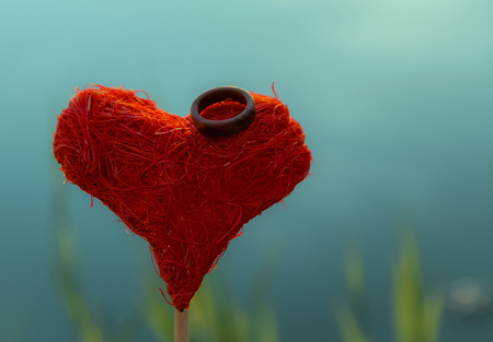 couple dating: Wooden wedding ring on a red hand made heart on a turquoise background out of focus