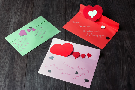 declaration: Three multi-colored envelope with a declaration of love written in different languages and paper hearts. Stock Photo